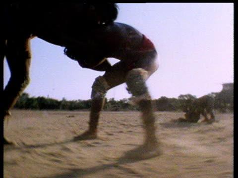 vídeos de stock, filmes e b-roll de mehinaku indians wrestling in desert wearing sumo type clothing partially silhouetted in evening sun - cultura indígena