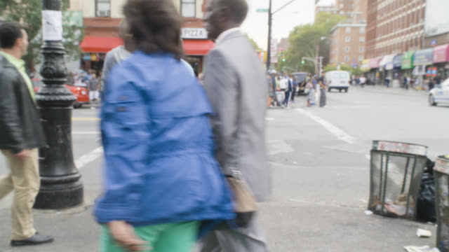 meidum angle of pedestrians crossing crosswalk of city street. car visible. crossing guard visible. restaurant visible in bg. out of focus.