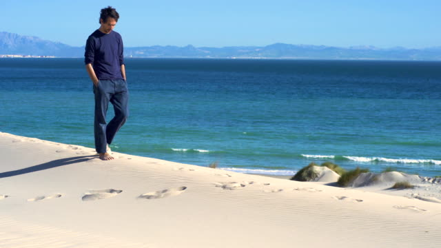 a melancholic young man walking in a dune sand with ocean and africa coast behind him - one mid adult man only stock videos & royalty-free footage