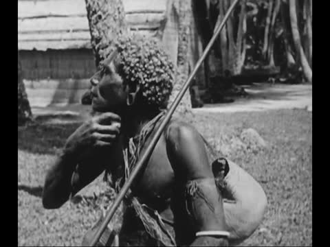 stockvideo's en b-roll-footage met melanesians fishing/ tribal people climbing up palm trees and picking coconuts/ tribal people drinking water/ indigenous people rubbing wood to make... - piercing