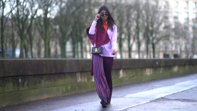 Melanie Darmon wears a pink blazer jacket purple striped pants a Vuitton clutch outside Valentino during Paris Fashion Week Womenswear Fall/Winter...