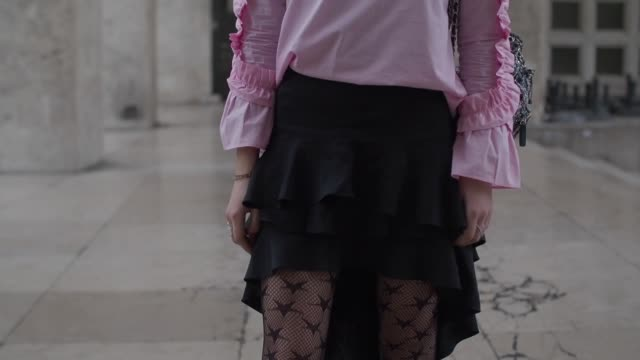 stockvideo's en b-roll-footage met melanie darmon wears a zara pink top with ruffles a zara bag a jacquemus black ruffled skirt asos black tights an asos headband louboutin heels shoes... - haarband
