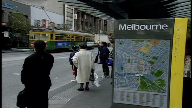 melbourne sign and street with trolleys going by - trolleybus stock-videos und b-roll-filmmaterial