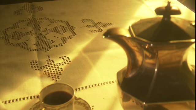 mellow sunlight glows across a table laden with tea service and a magazine. - アフタヌーンティー点の映像素材/bロール