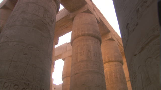 mellow sunlight illuminates the carved columns of karnak temple in egypt. - temples of karnak stock videos and b-roll footage