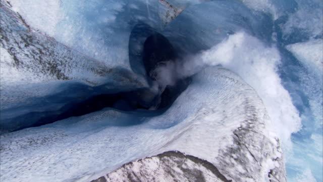 vídeos de stock, filmes e b-roll de melt water crashes over a ledge and into a deep ice hole. - neve derretida