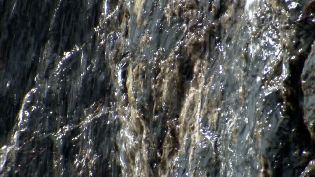 vídeos de stock, filmes e b-roll de melt water spills over a rock face. - neve derretida