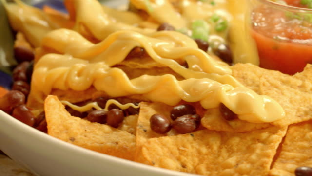ecu pan melted cheese poured over nachos of tortilla chips and beans - cheese stock videos & royalty-free footage