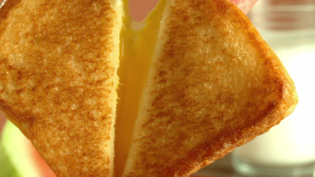Melted cheese stretches between two halves of a sandwich.