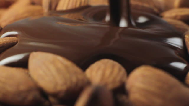 slo mo ecu melted chocolate being poured on almonds - almond stock videos & royalty-free footage