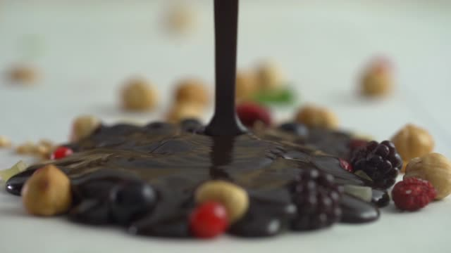 melted chocolate over hazelnuts and red fruits hd video - savoury sauce stock videos & royalty-free footage
