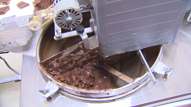 melted chocolate pours onto conveyor belt at terry's toffee in chicago on feb 10 2015 - karamell stock-videos und b-roll-filmmaterial
