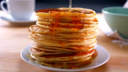 Melted golden honey is doused on just cooked pancakes on table, ready to be eaten