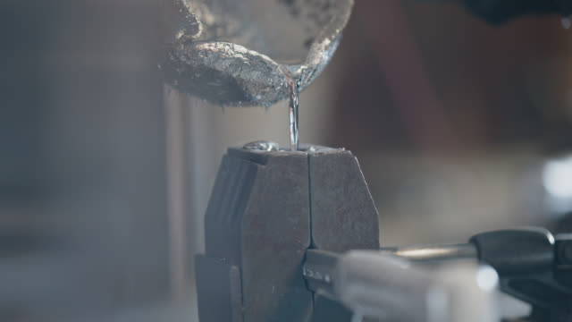 slo mo cu melted steel being poured into hammer mold - silver coloured stock videos & royalty-free footage