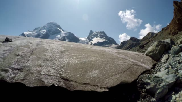 melting glacier with flowing water and snow capped mountains, klein matterhorn, swiss alps - macchina da presa manuale video stock e b–roll