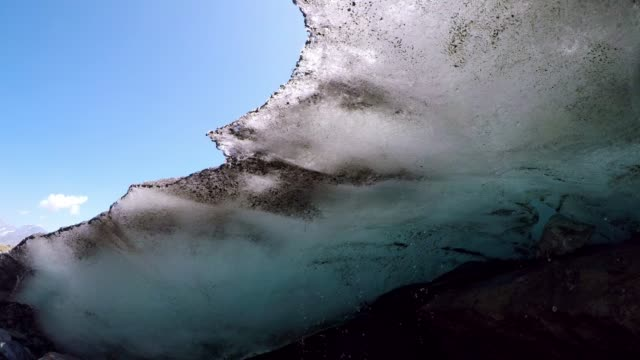 Melting glacier with water dripping from overhanging ice with blue sky, Swiss Alps