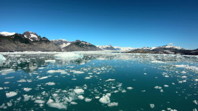 pov melting icebergs floating alaskan mountain range usa - pacific war stock-videos und b-roll-filmmaterial