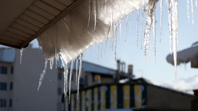 vídeos de stock, filmes e b-roll de derretendo o gelo e a luz do sol no topo de um telhado - pingente de gelo