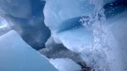 Melting of a glacier. Interior of an ice cave. Water flowing down from above with splashes. Slow motion shot