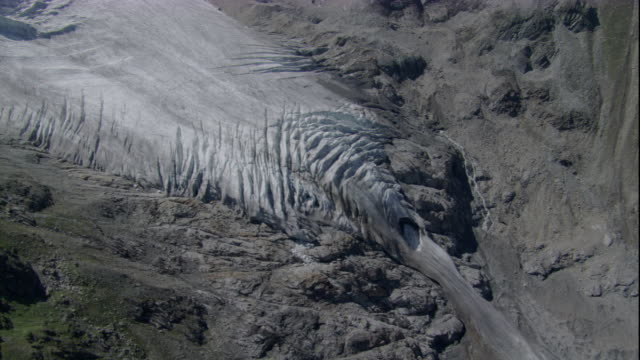 Meltwater flows from the terminal edge of a glacier in the Austrian Alps. Available in HD.