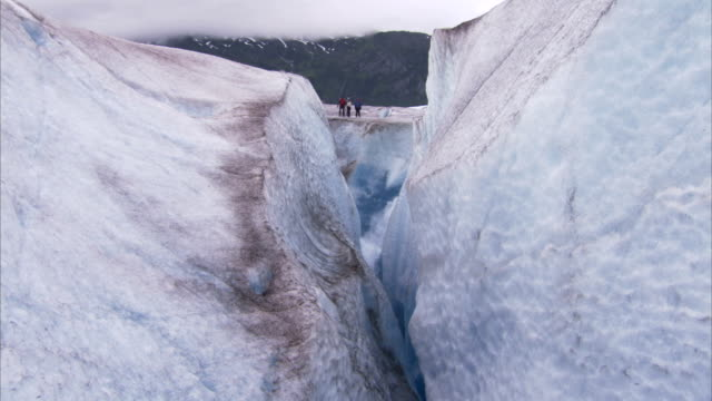 a meltwater stream flows into a crevasse where ice climbers stand on the edge. - crevasse stock videos & royalty-free footage