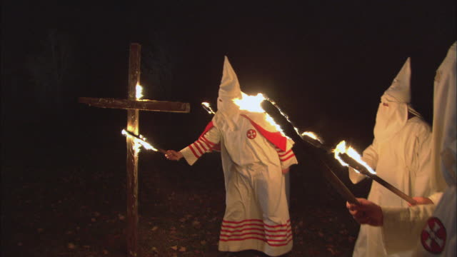 stockvideo's en b-roll-footage met recreation kkk member lighting a standing large, wooden cross as other members are holding torches and watching / rockford, illinois, united states - racisme