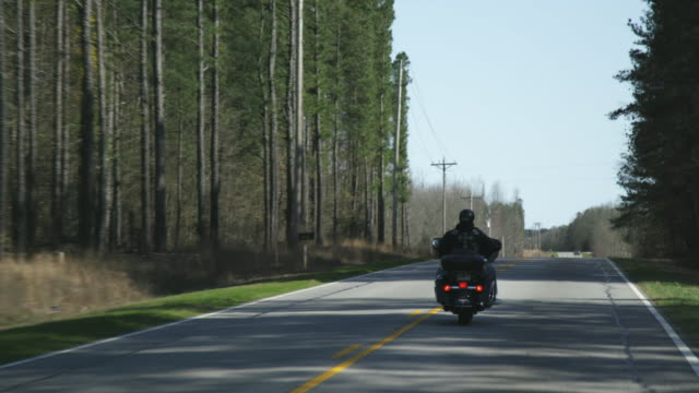 member of christian motorcycle club rides along highway - motorradfahrer stock-videos und b-roll-filmmaterial