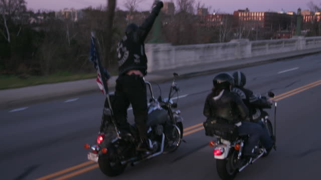vidéos et rushes de member of christian motorcycle club stands up on motorcycle as he rides along highway - motard