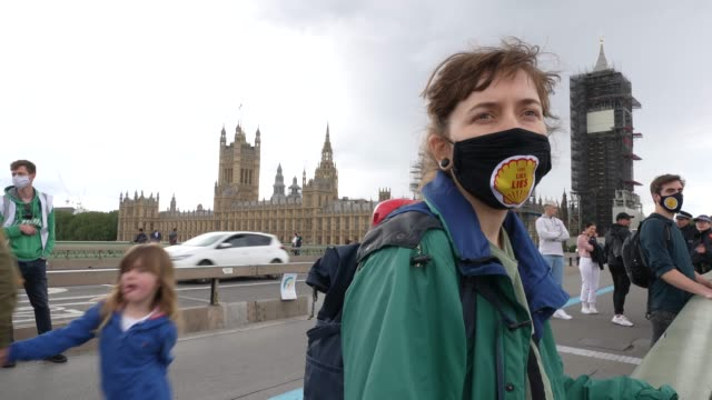 member of extinction rebellion holds part of a banner hung over westminster bridge protesting against multinational oil giant shell highlighting the... - environment stock videos & royalty-free footage