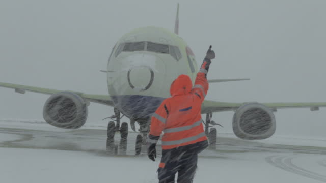 Member of ground crew is showing OK sign to pilot - selective focus