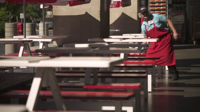 member of staff cleans picnic tables outside a costco, usa. - sonnenschirm stock-videos und b-roll-filmmaterial