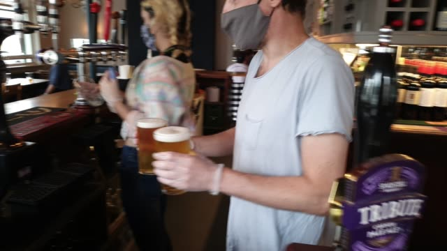 a member of staff wearing a face mask and gloves pours pints at the lordship pub east dulwich on july 4 2020 in london england the uk government... - utensil stock videos & royalty-free footage