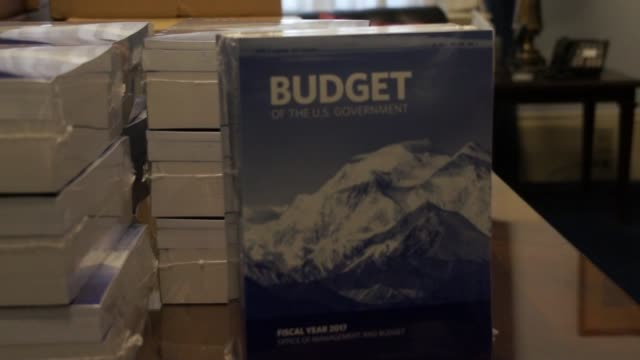 A member of the Government Publishing Office delivers bound copies of the final budget submission of President Barack Obama to Capitol Hill recived...