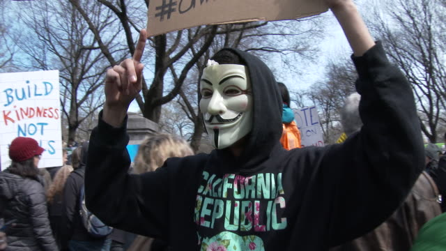 A member of the group 'Anonymous' wearing a mask holds up a sign claiming to display Donald Trump's social security number at an Anti Trump rally in...