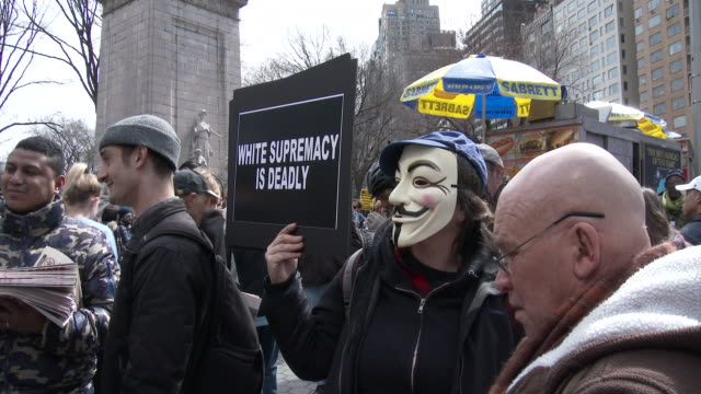 A member of the group 'Anonymous' wears a mask and holds a sign at an Anti Donald Trump rally in Columbus Circle Manhattan