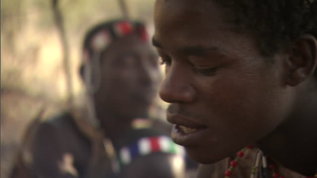a member of the hadza tribe peels a banana near smoke from a campfire in tanzania. - 民族衣装点の映像素材/bロール