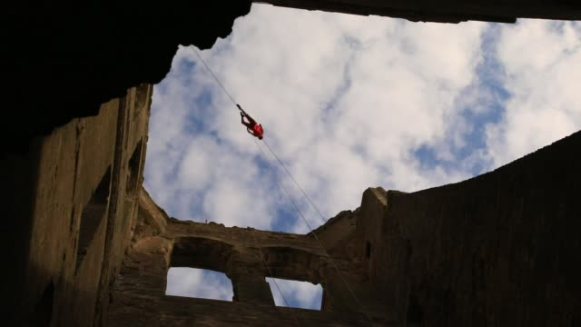 """member of the """"in fine"""" aerial dance company dances in the air above the ruined nave of the """"saint-mathurin church on september 20, 2020 in larchant,... - modern dancing stock videos & royalty-free footage"""