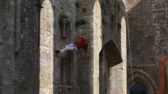 """member of the """"in fine"""" aerial dance company performs a choreography on the walls on the ruined nave of the """"saint-mathurin church on september 20,... - modern dancing stock videos & royalty-free footage"""