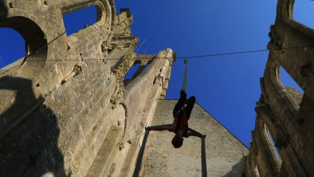 """member of the """"in fine"""" aerial dance company performs a choreography on a string in the ruined nave of the """"saint-mathurin church on september 20,... - modern dancing stock videos & royalty-free footage"""