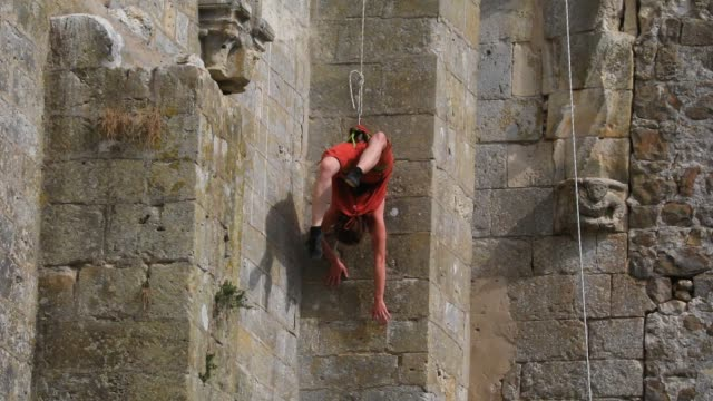 """member of the """"in fine"""" aerial dance company rappels down a wall on the ruined nave of the """"saint-mathurin church on september 20, 2020 in larchant,... - modern dancing stock videos & royalty-free footage"""