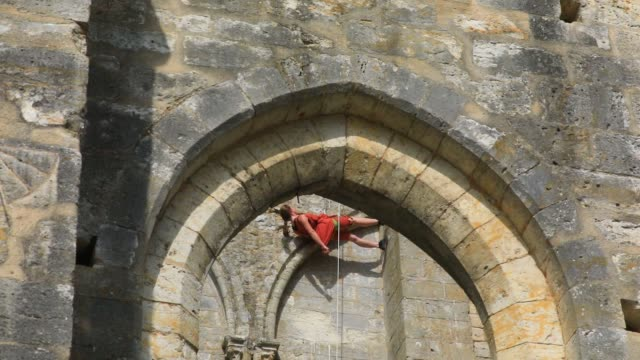 """member of the """"in fine"""" aerial dance company walks vertically on a wall of the ruined nave of the """"saint-mathurin church on september 20, 2020 in... - modern dancing stock videos & royalty-free footage"""