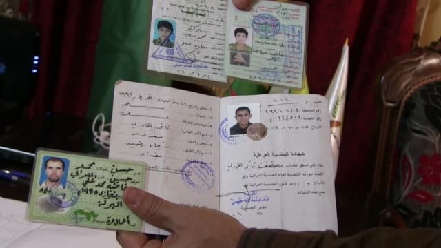 member of the kurdish ypg militia holds a collection of identity cards found on the bodies of isis or isil fighters at the headquarter of the kurdish... - people's protection units stock videos & royalty-free footage