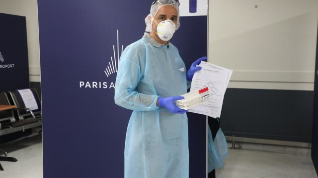 member of the medical staff shows a test during the installation of antigenic tests in french airports to detect travelers carrying covid-19 on... - mutazione genetica video stock e b–roll
