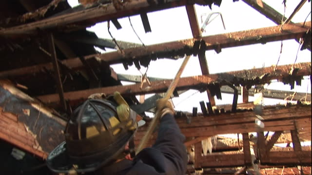 a member of the oakland fire department pulls rafters down with a rake-like tool in a burned-out building. - rubble stock videos & royalty-free footage