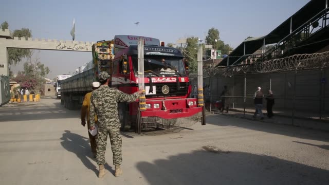 A member of the Pakistani security forces stops a truck to inspect documents at the Torkham border crossing between Pakistan and Afghanistan in...