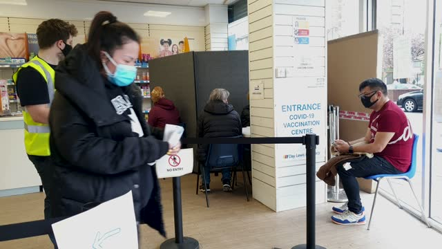 member of the public leaves after receiving her dose of the covid vaccine as others wait in a queue at the nhs vaccine centre at day lewis pharmacy,... - brian dayle coronavirus stock videos & royalty-free footage