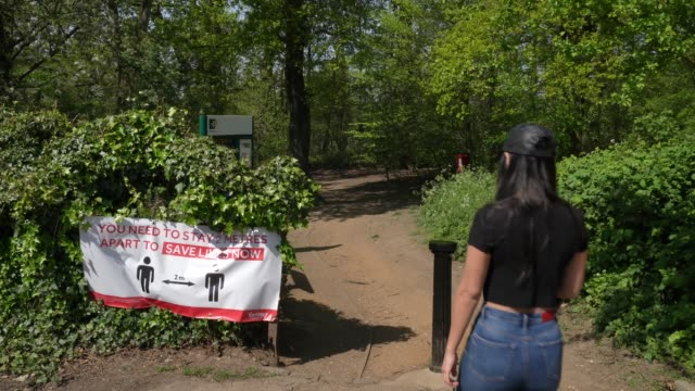 member of the public walks past a 2 meter social distancing sign outside bluebell woods in bounds green due to the covid-19 coronavirus pandemic. - forest stock videos & royalty-free footage