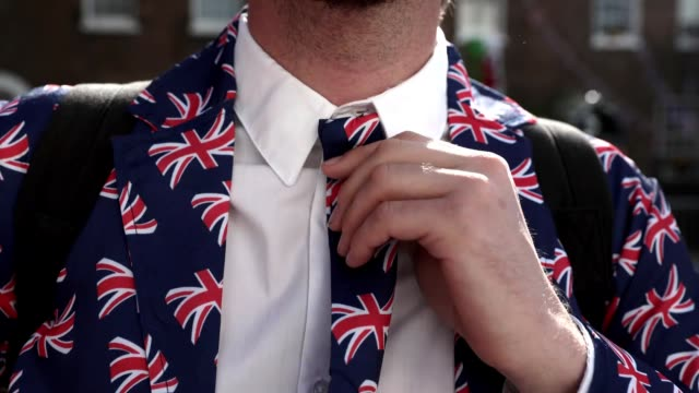 A member of the public wearing Union Jack colours adjusts his tie during the Royal wedding on May 19 2018 in Windsor England