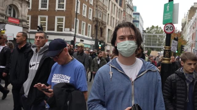 a member of the public wears a face covering / face mask as protesters show a lack of social distancing during a unite for freedom march on october... - human head stock videos & royalty-free footage