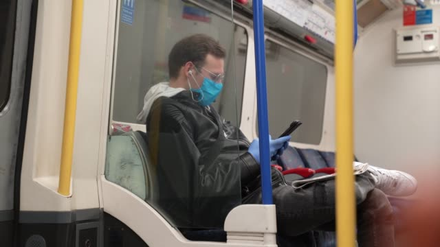 a member of the public wears a face mask and plastic gloves on the london underground at coronavirus outbreak in london on march 06 2020 in london... - glove stock videos & royalty-free footage